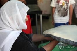 Друзская женщина в национальной одежде готовит друзскую лепешку - сначала тесто приводится в форму блина круговыми движениями ладонь рук.