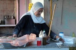 Друзская женщина в национальной одежде готовит друзские лепешки.