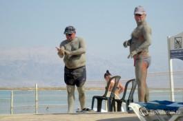 Отдыхающие мажутся грязью на Мертвом море.